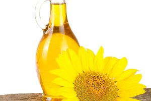 Sunflower oil and flower on wooden table with white background
