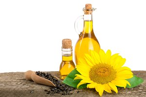 Sunflower oil, seeds and flower on wooden table with white background