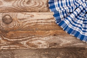 blue checkered tablecloth on the old wooden table with copy space for your text. Top view