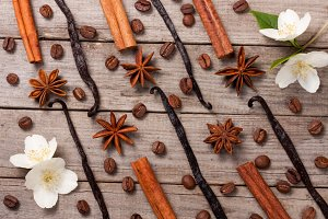 Vanilla sticks and cinnamon with anise and coffee beans on a old wooden background