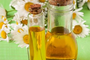 bottle with essential oil and fresh chamomile flowers on a green wooden background