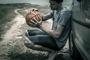 young man with basketball ball on the road, the emotions of the athlete
