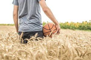 a young man with a basketball on the nature, concept of sport