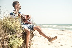 young man with acoustic guitar on the beach, the concept of leisure and creativity