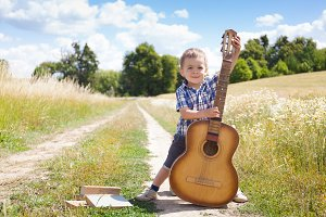 Beautiful little boy with guitar