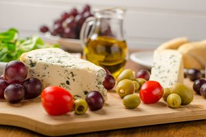 Delicious blue cheese with olives, grapes and salad