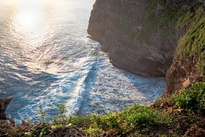 Sea cliff at sunset with beautiful sunlight on ocean shore. Scenic sea landscape, Bali tropical nature, Indonesia fantastic outdoor view