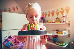 Little girl blows on toy cake candles
