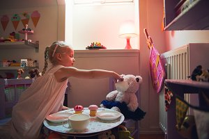 Girl playing tea-party with her toy bear