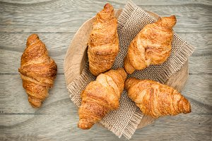 Fresh baked croissants on wood table