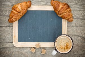 Cup of black coffee with croissant