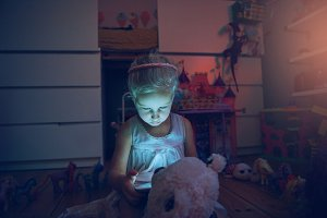 Child with tablet and bear at night