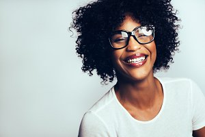 Laughing young African woman wearing glasses against a gray background