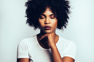 Attractive African woman standing with a hand on her chin