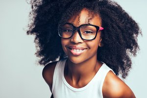 Cute little African girl wearing glasses against a gray background