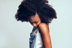 Shy young African girl standing sideways against a gray background