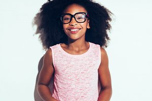 Smiling young African girl wearing glasses against a white background