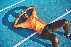 Tired young athletic lying on a running track after training