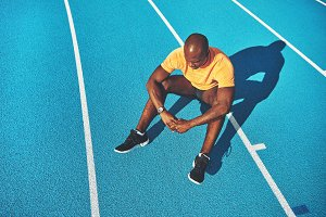 Young runner sitting alone on a running track after training