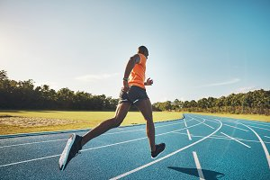 Fit athlete sprinting alone down a running track outside