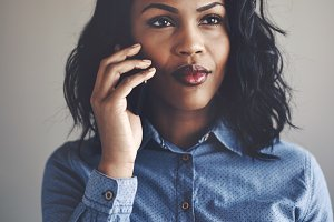 Focused young African businesswoman standing alone talking on a cellphone