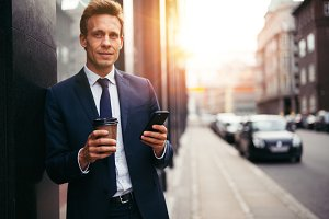 Smiling businessman sending texts and drinking coffee in the city
