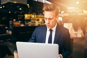 Young businessman drinking coffee and working online in a cafe