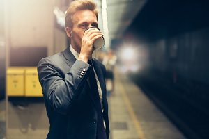 Businessman drinking coffee while waiting for a subway train