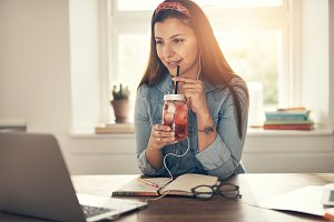 Smiling businesswoman at laptop with drinking jar