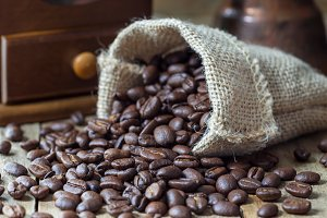 Fragrant coffee beans in a sack and on a wooden table, horizontal