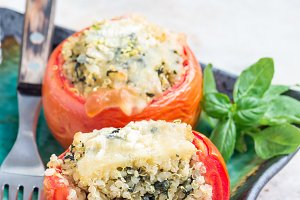 Baked tomatoes stuffed with quinoa and spinach topped with melted cheese on plate, vertical, copy space