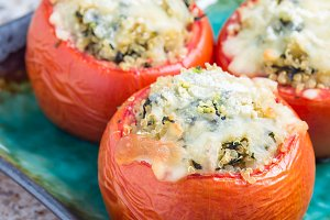 Baked tomatoes stuffed with quinoa and spinach topped with melted cheese on plate, vertical