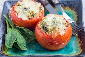 Baked tomatoes stuffed with quinoa and spinach topped with melted cheese on plate, horizontal