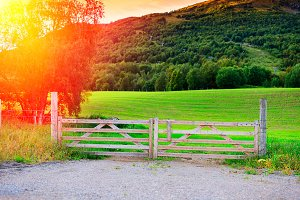 Farm entrance gate with light leak background