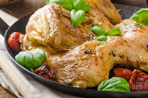 Chicken baked with tomatoes and basil on iron pan