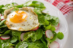 Fresh spinach, radish salad with fried egg