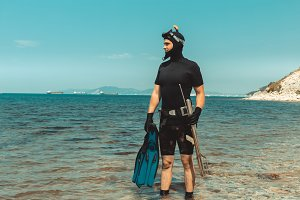 Young man, underwater hunter, dressed in a wet suit, keeps equipment in his hands and smotrithes into distance