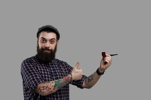 Tattooed biker show like and smoking pipe. Isolated big beard person. Attractive and smiling kind guy look into the camera. Stock worker on the break. Ready for relax time. Concept of smoke product.