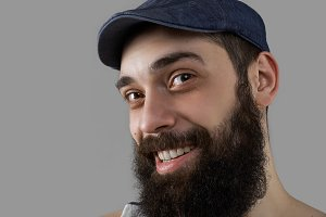 Close up portrait of happy and smiling bearded man in studio on grey background. Male have interesting and adventure life, like to travel and extreme hiking.