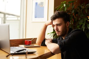 Boring freelancer search the job. Man in black tshirt sit in front of notebook and waiting new mail using modern laptop computer and wireless connection to internet or waiting meeting with girlfriend