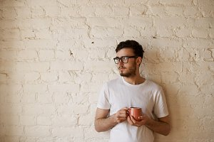 Student in eye glasses and white t-shirt stay with cap of tea in front of white brick wall and dream successful job. Copy space for advertising text of promotion product. Serious emotion on the face.
