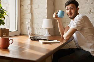 Crazy smiling beard young man in white t-shirt drinking coffee in modern interior and read funny blog. Man use internet technology to chat friends online video conversation.