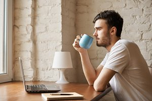 Cropped image of handsome copywriter with stylish beard holding cup with coffee in hand. Close up young man using laptop and using free internet connection to find new job or read news in morning