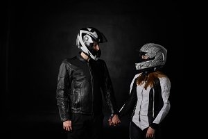 Portrait of bikers man and woman on black background. Motorcycle love concept. Extreme riders in leather jacket and suit hold hands and look at each other.