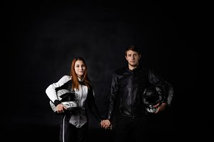 Portrait of biker man with girlfriend in motorcycle leather equipment and motorbike helmets hold hands and look to the camera. Moto goods and sport advertising concept. Bike lovers.