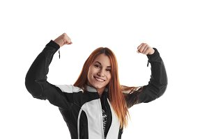 Happy and a lot of fun woman motorbiker. Femail in black and white protective dress with hands up on neutral background. Smiling girl with good mood. Win concept.