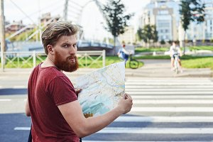 Tourist explore new city. Hansome man with big beard in red t shirt walk in the city to learn more about it. Guy stay in font of crosswalk and look back in sunny summer day.