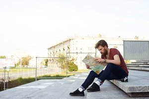 Handsome man read the map of european city on stone steps. Tourism or urban explore concept. Hipster bearded guy in red t shirt, dark blue jeans, white socks and black boots.
