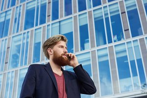 Attractive bearded man talk by mobile phone near business building with big blue windows. Serious guy like a boss in red t shirt and dark suit.