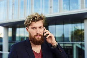 Bearded man look into the cameta and talk by mobile phone with business building background. Attractive hipster with smartphone stylish dress have conversation.